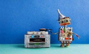 Robot chef de cuisine. poêle électronique poêle poêle. Jouets de conception créative, automatisation robotique futur concept de maison intelligente. Fond de plancher vert mur bleu. Banque d'images - 96143599